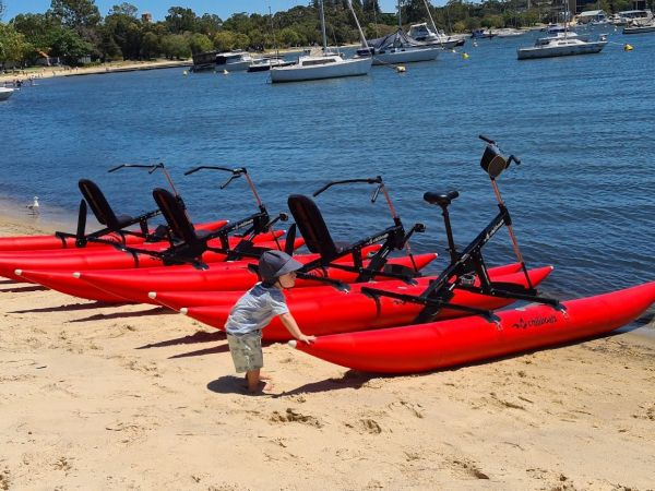 toddler with waterbikes on matilda bay foreshore.